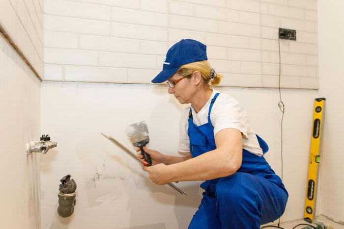 Маляр-штукатур выравнивает стену под покраску. Источник: mastera-remonta.com